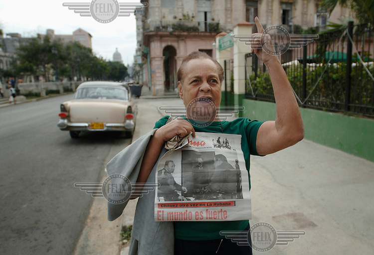 A woman triumphantly displays a newspaper depicting President Fidel Castro in a conversation with Venezuelan President Hugo Chavez. Despite persistent rumours to the contrary, the paper claims that Castro's health is improving.