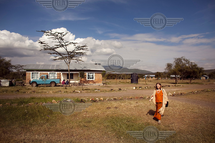 Gemma Enolengila walks towards her school. Gemma, who is British, worked with Lesikar Olengila (who is Masai) and later married him. Together, they operate a school, a shelter for women escaping female genital mutilation (FGM), and a travel company.