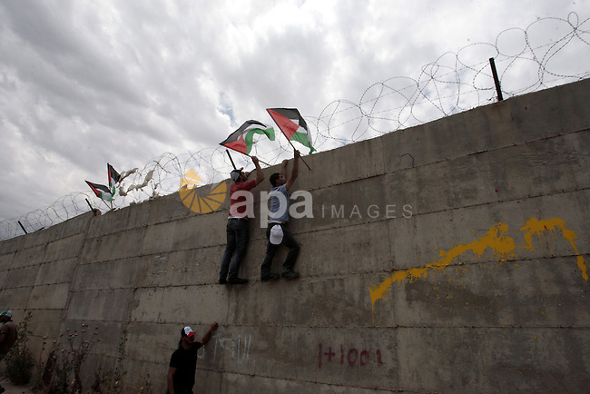 Palestinian demonstrators place a Palestinian flag on Israel's separation barrier during a march ahead of Nakba in the West Bank city of Tulkarem on May 13, 2013. Palestinians and Arab Israelis are preparing to mark Nakba Day on May 15 which commemorates the exodus of hundreds of thousands of their kin after the establishment of Israel state in 1948. Photo by Nedal Eshtayah