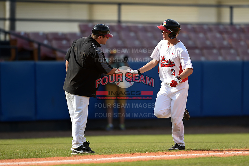 Illinois State Redbirds Jared Hendren (19) shakes hands with coach Mike Stalowy while running the bases on a Mason Snyder (not shown) home run during a game against the Bowling Green Falcons on March 11, 2015 at Chain of Lakes Stadium in Winter Haven, Florida.  Illinois State defeated Bowling Green 8-7.  (Mike Janes/Four Seam Images)