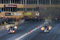Jul. 20, 2013; Morrison, CO, USA: NHRA top fuel dragster driver David Grubnic (left) races alongside Spencer Massey during qualifying for the Mile High Nationals at Bandimere Speedway. Mandatory Credit: Mark J. Rebilas-