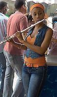 beautiful musician playing flute in a bar in Havana vieja.