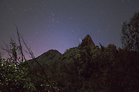 A mountain peak under a starry night sky near the Pali Lookout, O'ahu.
