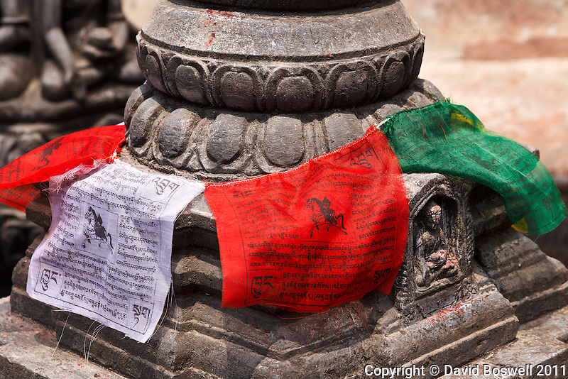 Prayer flags add a splash of color to a small scuplture at the Swayambhunath Temple, a Buddhist temple in Kathmandu, Nepal.