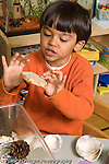 Preschool 3-4 year olds boy talking to himself as he plays with and looks at rocks, shells, pine cones and other natural materials in science area vertical