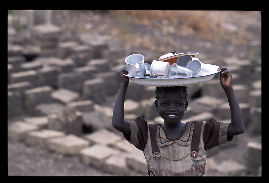 A Sudanese refugee belonging to the Uduk tribe, carries washed dishes on her head.
