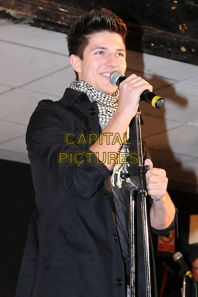JOSH DUBOVIE .Switches on the Christmas lights in  Basildon, Essex, England, UK, .18th November 2010.music performing concert gig live on stage half length black jacket trench coat  white scarf microphone singing .CAP/BRC.©Ben Rector/Capital Pictures.