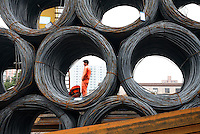 Workers unload rolls of steel wire from a train carriage at a steel wholesaler market in Shanghai, China..06 Nov 2007