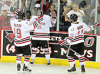 Nebraska Omaha's Ryan Walters (19) and Jayson Megna (11) celebrate Josh Archibald's (15) first collegiate goal during the second period of UNO's game against Mercyhurst. (Photo by Michelle Bishop) . .