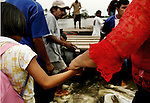 """A mother holds her daughter's hand as they get ready to board a raft to visit relatives and friends in Mexico on Tuesday, May 8, 2007, in Tecun Uman, Guatemala. For those who can't go to Mexico legally cross the river by raft, or """"camara,"""" in Spanish, for 10 quetzales, or about one dollar and thiry cents each way."""