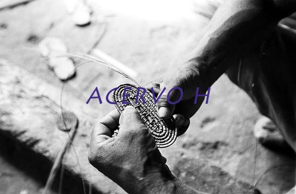 &Iacute;ndio Werekena, morador da comunidade de Anamoim no alto rio Xi&eacute;,come&ccedil;a com sua fam&iacute;lia o trabalho de beneficiamento da pia&ccedil;aba (Leopold&iacute;nia p&iacute;assaba Wall), para trnsform&aacute;-la em artesanato . A fibra  um dos principais produtos geradores de renda na regi&atilde;o &eacute;  coletada de forma rudimentar. At&eacute; hoje &eacute; utilizada na fabrica&ccedil;&atilde;o de cordas para embarca&ccedil;&otilde;es, chap&eacute;us, artesanato e principalmente vassouras, que s&atilde;o vendidas em v&aacute;rias regi&otilde;es do pa&iacute;s.<br />Alto rio Xi&eacute;, fronteira do Brasil com a colombia  a cerca de 1.000Km oeste de Manaus.<br />06/06/2002.<br />Foto: Paulo Santos/Interfoto Expedi&ccedil;&atilde;o Werekena do Xi&eacute;<br /> <br /> Os &iacute;ndios Bar&eacute; e Werekena (ou Warekena) vivem principalmente ao longo do Rio Xi&eacute; e alto curso do Rio Negro, para onde grande parte deles migrou compulsoriamente em raz&atilde;o do contato com os n&atilde;o-&iacute;ndios, cuja hist&oacute;ria foi marcada pela viol&ecirc;ncia e a explora&ccedil;&atilde;o do trabalho extrativista. Oriundos da fam&iacute;lia ling&uuml;&iacute;stica aruak, hoje falam uma l&iacute;ngua franca, o nheengatu, difundida pelos carmelitas no per&iacute;odo colonial. Integram a &aacute;rea cultural conhecida como Noroeste Amaz&ocirc;nico. (ISA)