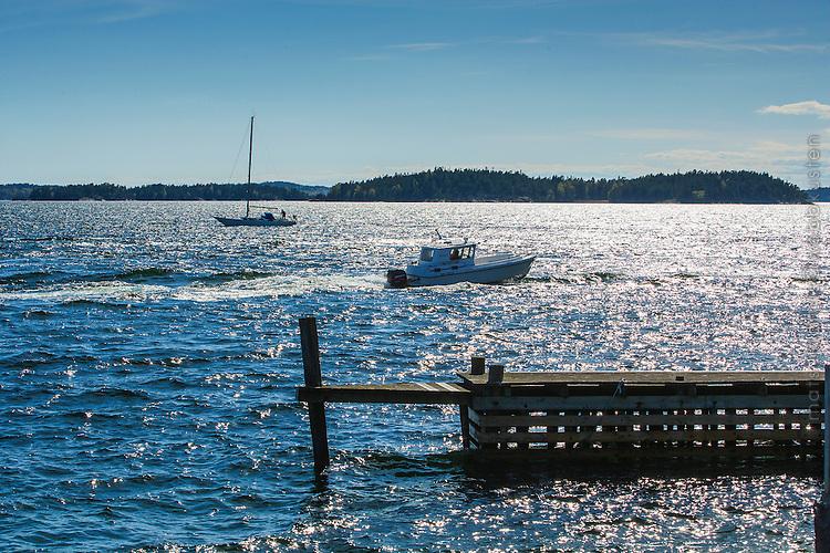 Två båtar går förbi en btygga på Dalarö  Stockholms skärgård. / Stockholms archipelago Sweden.