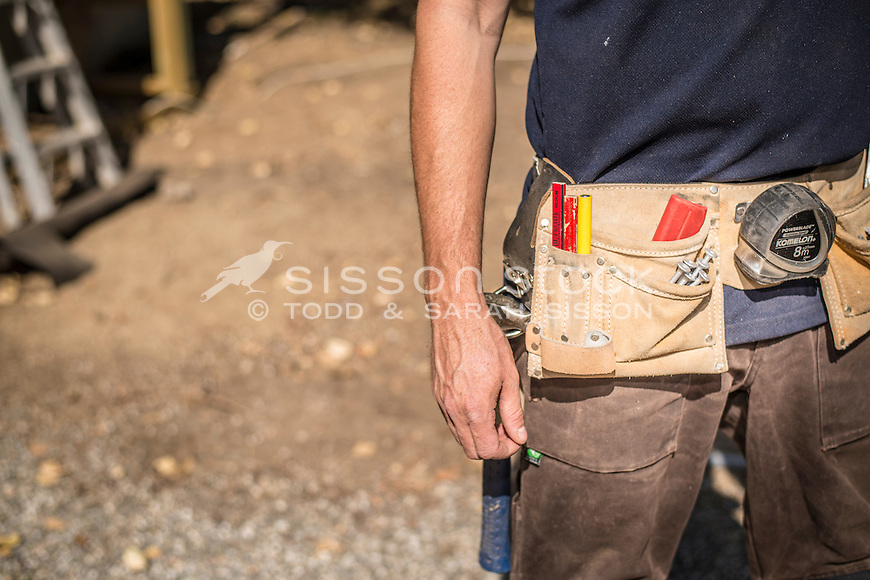 Home handyman wearing  tool belt, working outside on renovation project, New Zealand - stock photo, canvas, fine art print