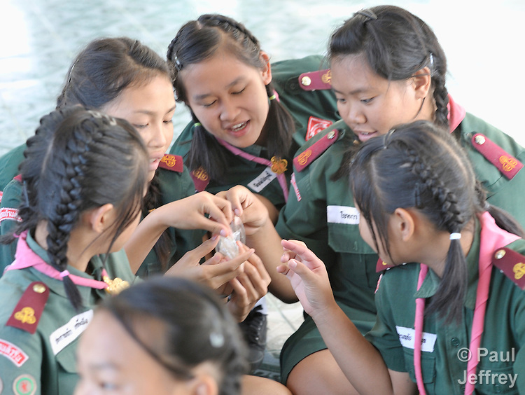Wearing their scouting uniforms, girls in the village of Toong-sa-tok in northern Thailand learn about HIV and AIDS during a session at the temple-supported Banhuarin School. Here they examine a female condom.
