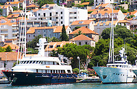 A very big luxurious pleasure motor boat yacht ship, blue and white, American registered with flag, with villas in the background, moored at the dock key. Modern apartment buildings and hotel in the background. Luka Gruz harbour. Dubrovnik, new city. Dalmatian Coast, Croatia, Europe.