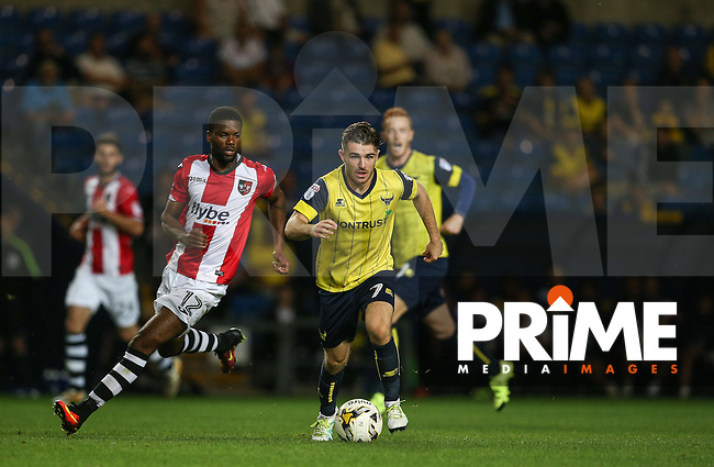 Dan Crowley of Oxford United heads away from Joel Grant of Exeter City during the The Checkatrade Trophy match between Oxford United and Exeter City at the Kassam Stadium, Oxford, England on 30 August 2016. Photo by Andy Rowland / PRiME Media Images.