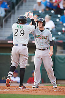 Norfolk Tides Corban Joseph (5) high fives Francisco Pena (29) after hitting a home run during a game against the Buffalo Bisons on July 18, 2016 at Coca-Cola Field in Buffalo, New York.  Norfolk defeated Buffalo 11-8.  (Mike Janes/Four Seam Images)