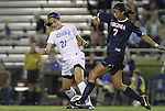 29 September 2011: Virginia's Gloria Douglas (7) knocks the ball away from Duke's Gilda Doria (21). The Duke University Blue Devils and the University of Virginia Cavaliers played to a 0-0 tie after overtime at Koskinen Stadium in Durham, North Carolina in an NCAA Division I Women's Soccer game.