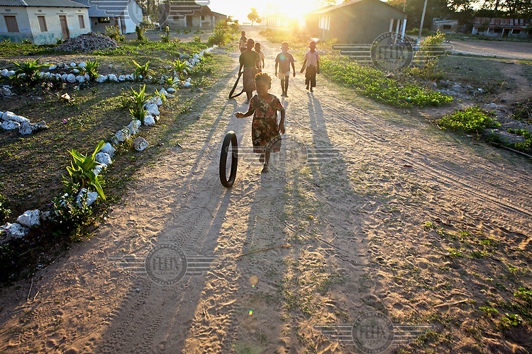 Children play with used bicycle tyres in their village on Ibo Island.