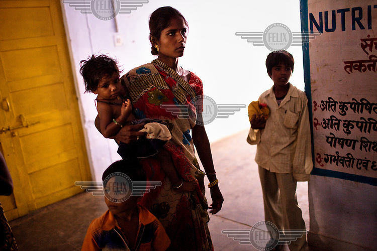 Jaikunwar holds her 15 month old malnutritioned daughter Anjana outside the nutritional rehabilitation centre in the pediatric ward at the Community Health Centre (Block Hospital) in Talbehat. The Indian government spends $1.4 billion a year on programs that include weighing newborn babies, counseling mothers on healthy eating and supplementing meals, but none of this seems to be yielding results.