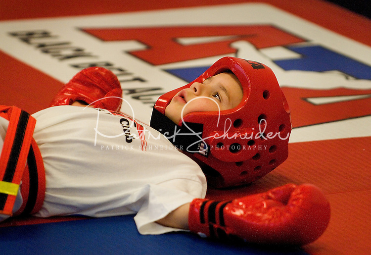 A young boy takes a break from class during a lesson in tae kwan do. Photo taken as part of an ATA class in Huntersville, NC.