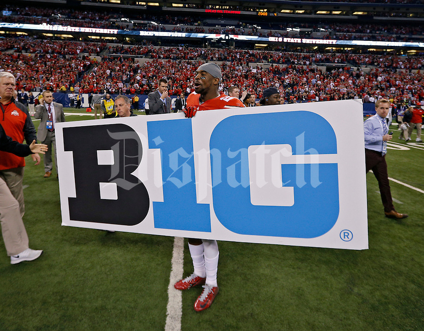 Ohio State Buckeyes safety Tyvis Powell (23) holds up a sign after beating Wisconsin Badgers 59-0 in the 2014 Big Ten Football Championship Game at Lucas Oil Stadium in Indianapolis, Ind. on December 6, 2014.  (Dispatch photo by Kyle Robertson)
