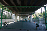 Kids play baseball in a small play area set up under the concrete of an expressway overpass in Hiroo, Tokyo, Japan. Friday May 30th 2014