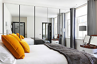 A bedroom with mirrored, floor-to-ceiling wardrobes that make the room apperar much larger
