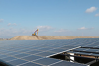 Solar panels in front of a digger being used to raise the level of the land against  future tsunami near Sendai, Miyagi, Japan. Friday March 11th 2016. The magnitude 9, Great East Japan earthquake struck at 2:46 on March 11th 2011 and caused  a tsunami that flattened  large parts of the Tohoku coast killing around 18,000 people and caused and nuclear disaster at Fukushima Daichi Power station. Solar farms are being built in the affected areas which will not be used as residential or agricultural  land again.