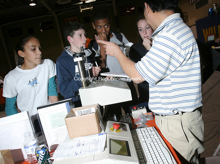 TORRINGTON, CT 26 October 2005 -102605BZ02- From left- Sam Amoroso, 14, gr. 9; Chad Hall, 14, gr. 9; Aaron Montgomery, 14, gr. 9; and Ally Pellegrino, 16, gr. 10; listen as Tung Duong, of Howmet Castings, describes how he will make engraved &quot;dog tags&quot;  for them at Oliver Wolcott Tech during Technology Day Wednesday.    <br /> Jamison C. Bazinet Republican-American