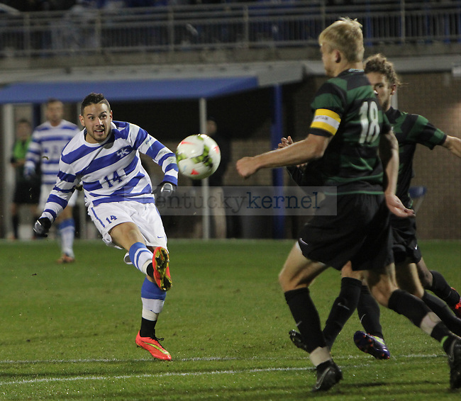 Junior Midfielder, Bryan Celis (14) rips a shot between Charlotte defenders during the UK vs. Charlotte mens soccer game for the Conference USA title. Friday, November 7, 2014 in Lexington. Photo by Joel Repoley   Staff