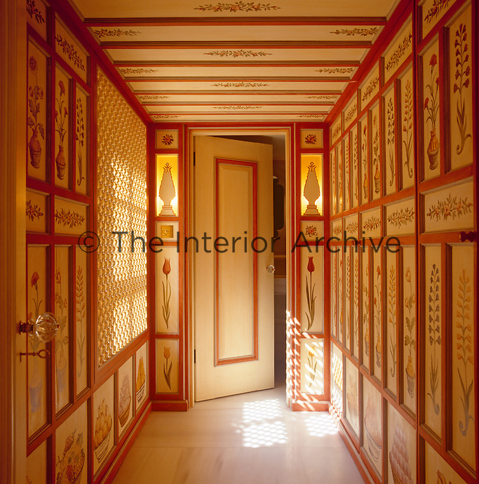 Geometrically patterned light falls across the marble floor and walls of this print-lined corridor