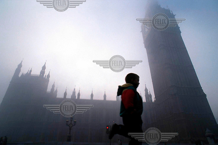 A boy skipping past Big Ben and the Houses of Parliament, Westminster, in the fog.