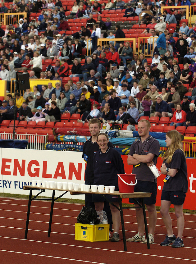 Photo. Jed Wee..Norwich Union British Grand Prix, 27/06/2004..Volunteers, with Sport England board, crowd in background.