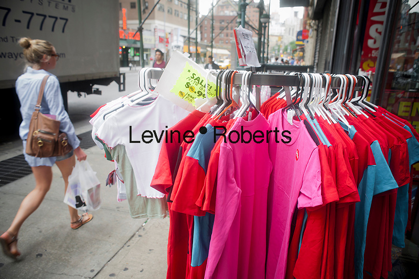 A shopper passes a display outside a store on Broadway in Greenwich Village in New York on Sunday, September 5, 2011.  (© Richard B. Levine)