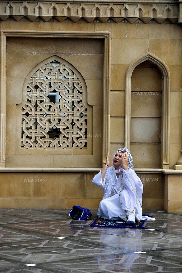 Azerbaijan, Baku, Shikov, Teze Pir Mosque, August 9, 2013<br /><br />Women pray in the courtyard of the Teze Pir mosque on the last day of Ramadan, known as &ldquo;Eid al-Fitr.&rdquo; The mosque was constructed from 1905-1914. The idea and funding for the mosque was provided by a female, Azeri philanthropist, Nabat Khanum Ashurbeyov. Only three years after it opened, the mosque was forced to function as a cinema and barn due to the 1917 October Revolution. Since 1943 it has reclaimed its function as a Shia mosque.  <br /><br />Azerba&iuml;djan, Bakou, Shikov, Mosqu&eacute;e Teze Pir , 9 Ao&ucirc;t 2013<br /><br /><br />Une Femme prie dans la cour de la mosqu&eacute;e Teze Pir au dernier jour du Ramadan, connu sous le nom de &laquo; 'A&iuml;d al-Fitr. &raquo; La mosqu&eacute;e a &eacute;t&eacute; construite entre 1905 et 1914. Son projet et son financement sont le fruit tu travail d'une femme philanthrope az&eacute;rie, Nabat Khanum Ashurbeyov. Seulement trois ans apr&egrave;s son ouverture, la mosqu&eacute;e a &eacute;t&eacute; contrainte de devenir un cin&eacute;ma et une grange en raison de la R&eacute;volution d'Octobre 1917. Depuis 1943, elle a repris son r&ocirc;le initial comme mosqu&eacute;e chiite.