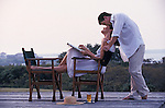 Grainy image of a romantic couple on deck of their vacation home.
