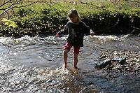 Mädchen, Kind im Bach, Kinder einer 2. Grundschulklasse machen einen Schulausflug an einen Bach im Frühling und genießen das frische, kalte Wasser