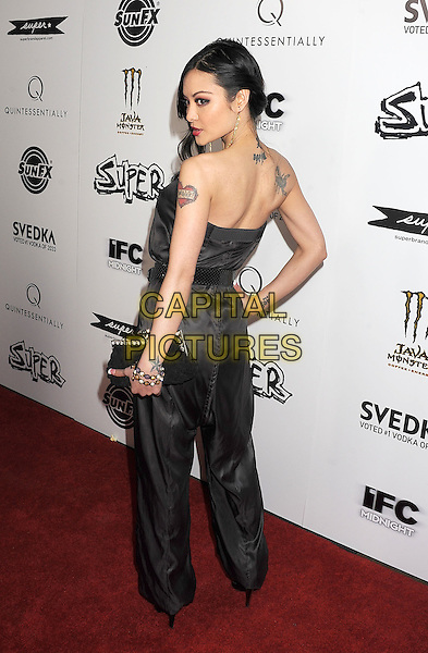 "TILA TEQUILA .arriving at the Los Angeles premiere of ""Super"" at the Egyptian Theatre in Hollywood, California, USA,.March 21st, 2011.  .full length strapless grey gray silk jumpsuit pantsuit belt black  sandals open toe clutch bag hand tattoo on hip side rear behind over shoulder back .CAP/ROT/TM.©TM/Roth Stock/Capital Pictures"