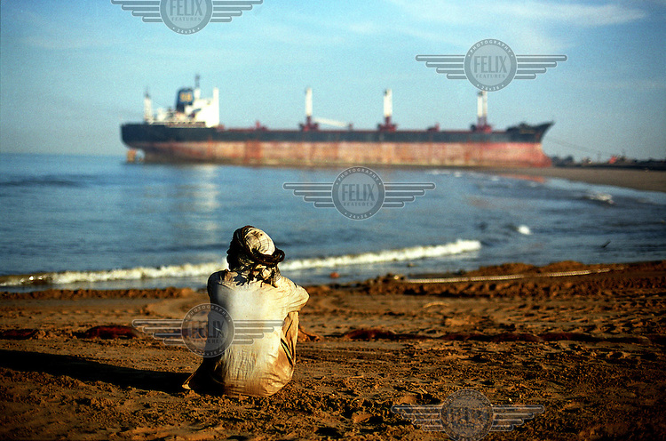 A worker rests on the beach beside the ship-breaking yard in Gaddani.