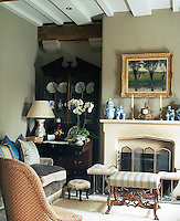 A velvet sofa adds to the comfort of the living room where a collection of blue and white china is displayed in an antique dresser and on the mantelpiece of the stone fireplace