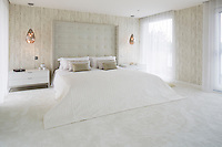 The master suite is a calm and tranquil space in off whites and neutrals. A winged headboard has been added to the super-king size bed, in a silver embossed faux animal skin fabric to gently frame the room, studded on the leading edges with rows of small chrome studs for definition. The walls are finished in softly textured vinyl wallpaper with hints of distressed wood cladding. As walls of glass flank both sides of the bedroom, full length white sheers were made to filter sunlight and add a calming elegance to the space. Warmth was added by faceted copper glass pendant chandelier lights. The sheers running in clean pocket headers either side of the master bedroom soften the edges.