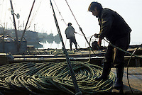 Nets and ropes are moved off fishing boats in harbour at Chuwang fishing village 250 km from Beijing. The Chinese fishing industry is in decline with Government about to cut 10% of boats, which amounts to 10,000 boats and 30,000 fishermen. Most boats in Chuwang have have not been put to sea for two weeks.