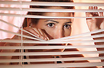 woman with worried face looking out window through venetian blinds
