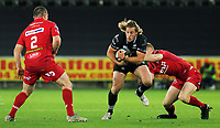 (L-R) Ken Owens of the Scarlets watches on as Jeff Hassler of the Ospreys is brought down by Johnny McNicholl of the Scarlets during the Guinness PRO14 Round 6 match between Ospreys and Scarlets at The Liberty Stadium , Swansea, Wales, UK. Saturday 07 October 2017