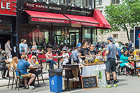 Local businesses Five Napkin Burger and Jacob's Pickles move out into the street during a street fair in the Upper West side neighborhood of New York on Sunday, May 28, 2017. (© Richard B. Levine)
