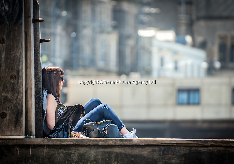 UK Weather: Aberystwyth, Ceredigion, West Wales Monday 18th July 2016. A young woman is relaxing by the promenade. The RNLI are out in force both making sure people are safe and raising awareness of the work they do.  Although it is overcast the sun is breaking through and the temperatures are expected to hit the low 20C with the mini heat wave expected to continue tomorrow reaching 30