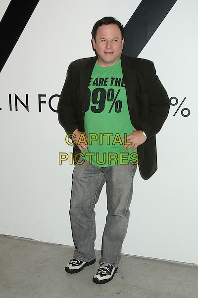 Jason Alexander.All In For The 99 Percent Event hosted by Van Jones, Rebuild The Dream and MoveOn.org held at 400 S La Brea, Los Angeles, California, USA, .31st March 2012..full length green t-shirt jeans grey gray jacket hand on hips slogan trainers .CAP/ADM/BP.©Byron Purvis/AdMedia/Capital Pictures.