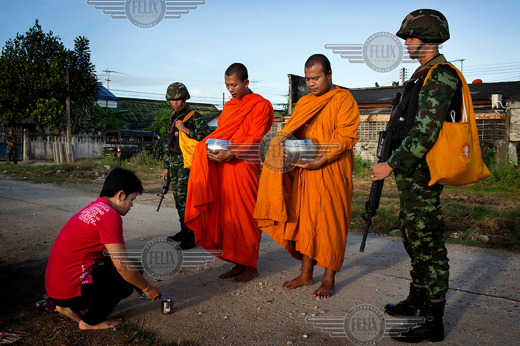 Soldiers from the 23rd Battalion of the Thai Army provide security as monks from the Lak Muang Temple collect alms in Pattani. /Felix Features