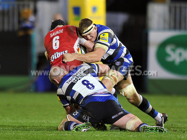 Tom Savage is double-tackled by Stuart Hooper and Carl Fearns. Aviva Premiership match, between Bath Rugby and Gloucester Rugby on October 25, 2013 at the Recreation Ground in Bath, England. Photo by: Patrick Khachfe / Onside Images